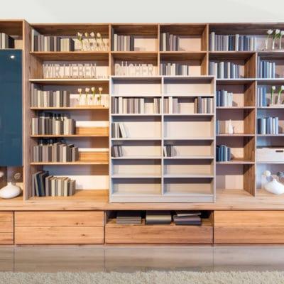 moderne Wohnwand aus Eiche massiv mit Schieberegal und Farbglastüren
