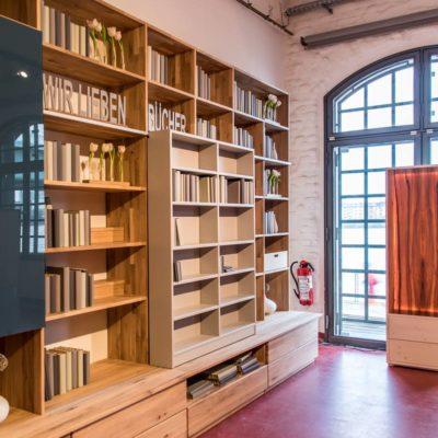 Wohnwand in Kernbuche massiv mit vorgesetztem Schiebebücherregal